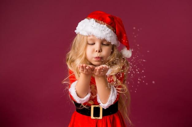 Menina loira em uma roupa de papai noel sopra neve das mãos
