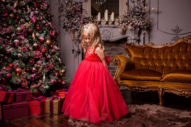 Menina loira em vestido vermelho perto da árvore de natal