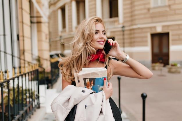 Menina loira encantadora com uma pequena tatuagem no braço falando no telefone e olhando para longe com um lindo sorriso