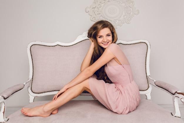Menina loira encantadora sentada em um sofá. ela tem cabelos longos e encaracolados e mantém as mãos nas pernas.