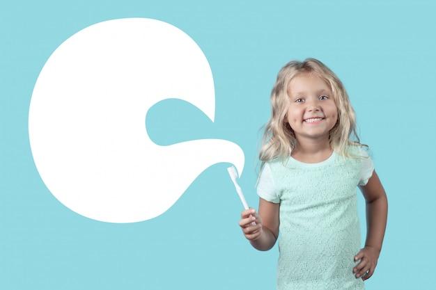 Menina loira encaracolada com um sorriso mostra como escovar os dentes.