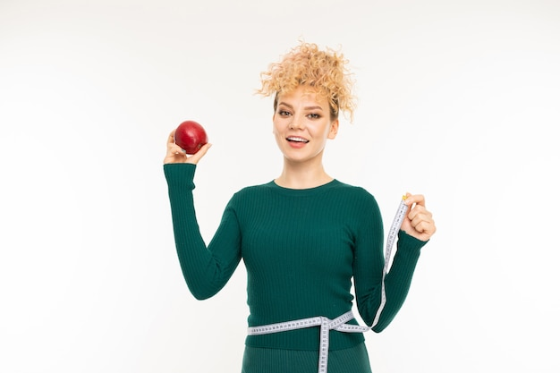 Menina loira encaracolada com uma boa figura detém uma maçã vermelha na mão na parede branca