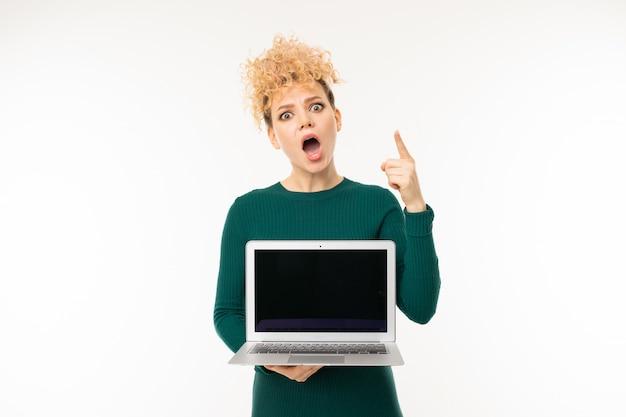 Menina loira encaracolada segurando um laptop com maquete com a tela para a frente em branco