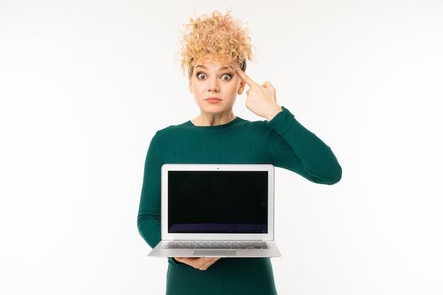 Menina loira encaracolada segurando um laptop com maquete com a tela para a frente na parede branca