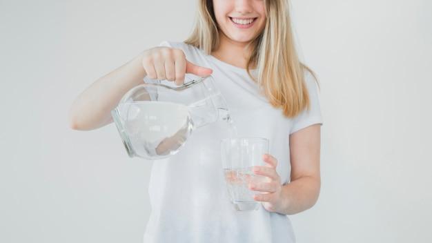 Menina loira, enchendo o copo de água