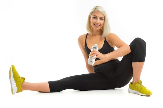 Menina loira entra para esportes com um uniforme esportivo preto com uma garrafa de água