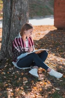 Menina loira, escrevendo em um caderno