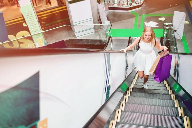 Menina loira está subindo na escada rolante