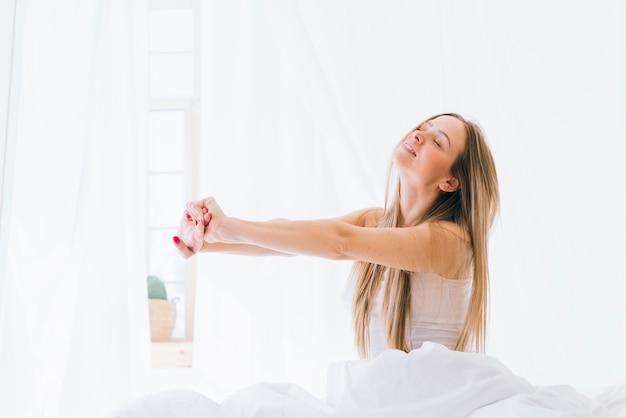 Menina loira, estendendo-se na cama