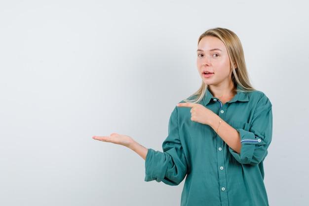 Menina loira, esticando as mãos como se estivesse segurando algo e apontando para ele na blusa verde e olhando sério.