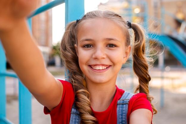 Menina loira, esticando as mãos para a câmera