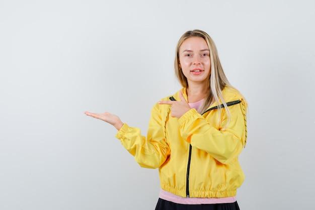 Menina loira esticando uma mão enquanto segura algo e apontando para ela com o dedo indicador em uma camiseta rosa