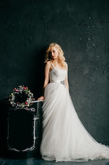 Menina loira europeia em retrato de estúdio de vestido de casamento branco.