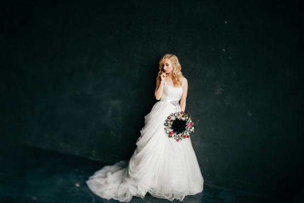 Menina loira europeia vestido de noiva branco segurando boquet de flores decorativas em fundo preto.