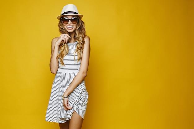 Menina loira expressiva em vestido branco, chapéu e óculos de sol
