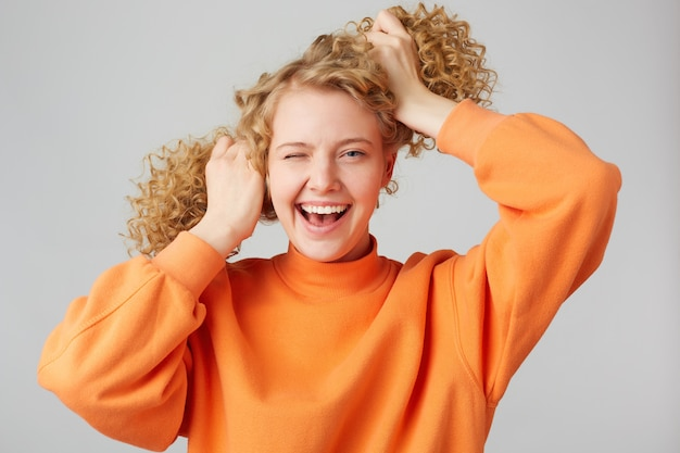 Menina loira extraordinária, enérgica e resiliente rindo de alegria, pisca e segura os cabelos cacheados fazendo duas caudas