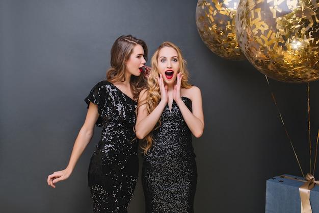 Menina loira fascinante em traje de luxo, passando o tempo em uma festa com o melhor amigo. garota atraente loira com vestido preto, posando com cara de surpresa durante o evento.