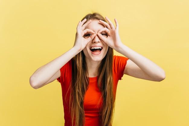 Menina loira fazendo óculos com os dedos