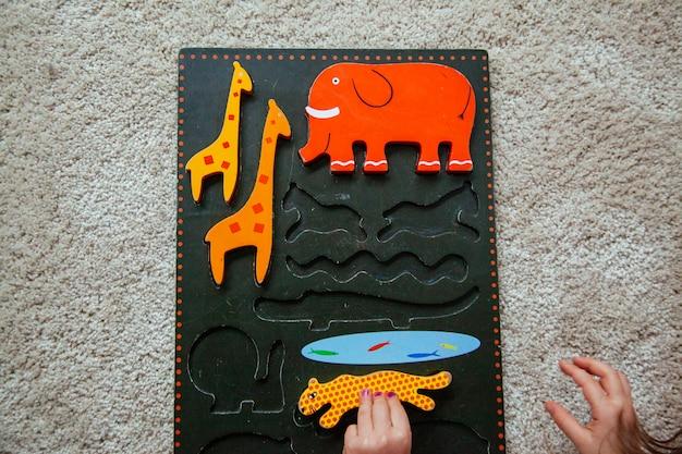 Menina loira fazendo um quebra-cabeça animal