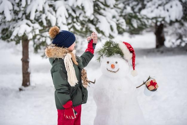 Menina loira feliz e fofa brincando com um boneco de neve