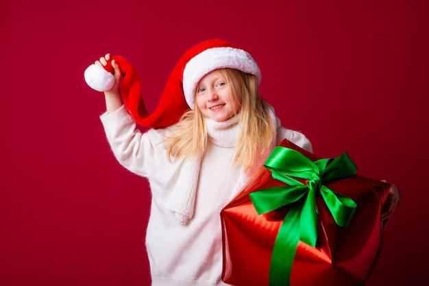 Menina loira feliz em um chapéu de papai noel segurando um presente de ano novo em uma parede vermelha
