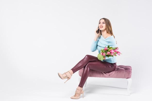 Menina loira feliz falando ao lado do telefone com lindas tulipas cor de rosa