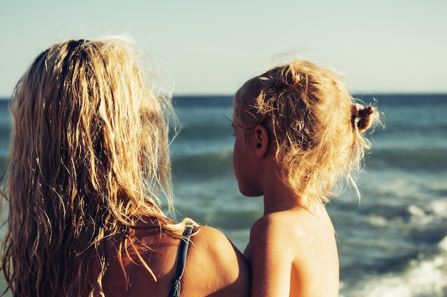 Menina loira feliz nos braços da mãe na praia. conceito de uma família feliz. férias concep
