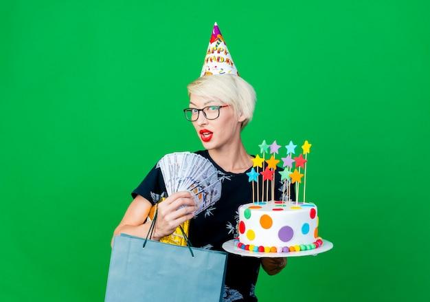 Menina loira festeira impressionada de óculos e boné de aniversário segurando um bolo de aniversário com estrelas, caixa de presente de dinheiro e saco de papel olhando para a câmera