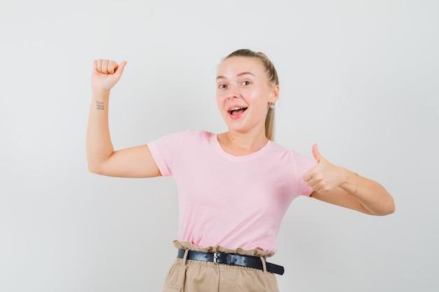 Menina loira fingindo segurar algo, aparecendo o polegar em uma camiseta, calça, vista frontal.