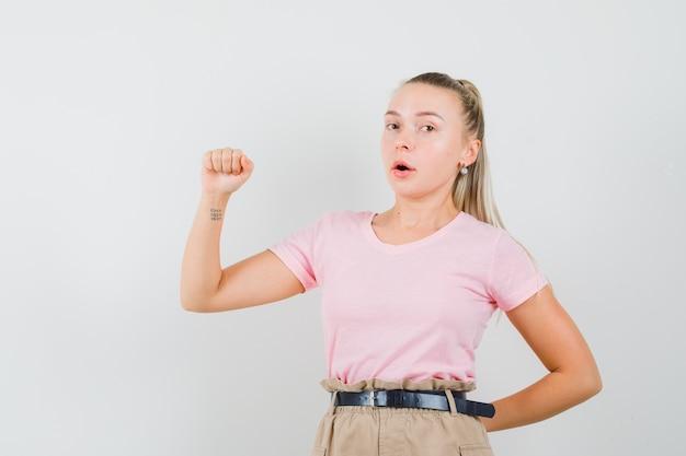 Menina loira fingindo segurar ou mostrar algo em uma camiseta, calça, vista frontal.
