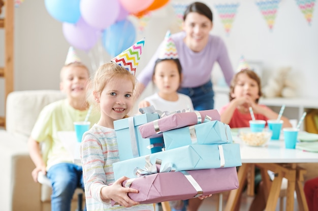 Menina loira fofa com presentes de aniversário em pé durante uma festa em casa com os amigos
