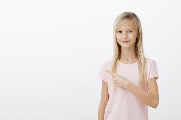 Menina loira fofa feliz apontando o dedo para a esquerda