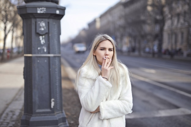 Menina loira fumando no inverno