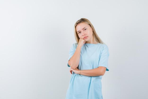 Menina loira inclinando a papada na palma da mão, em pé na pose de pensamento em t-shirt azul e olhando pensativa, vista frontal.