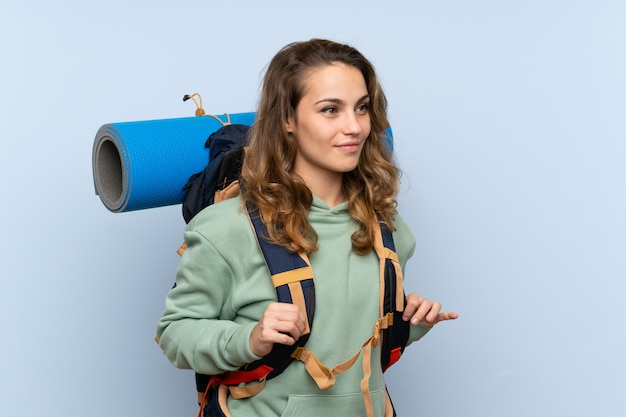 Menina loira jovem alpinista sobre parede azul isolada