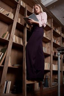 Menina loira jovem e atraente lê um livro para a biblioteca