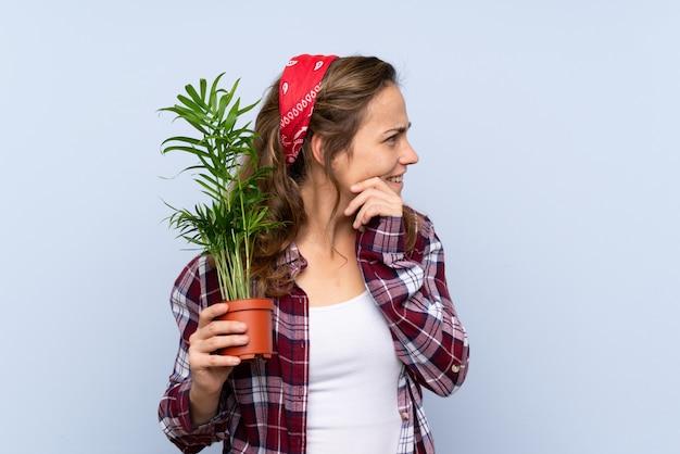 Menina loira jovem jardineiro segurando uma planta pensando uma idéia e olhando de lado