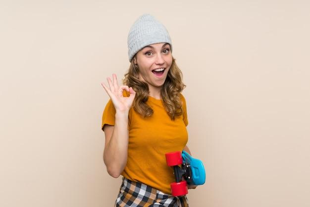 Menina loira jovem patinadora fazendo sinal bem sobre parede isolada