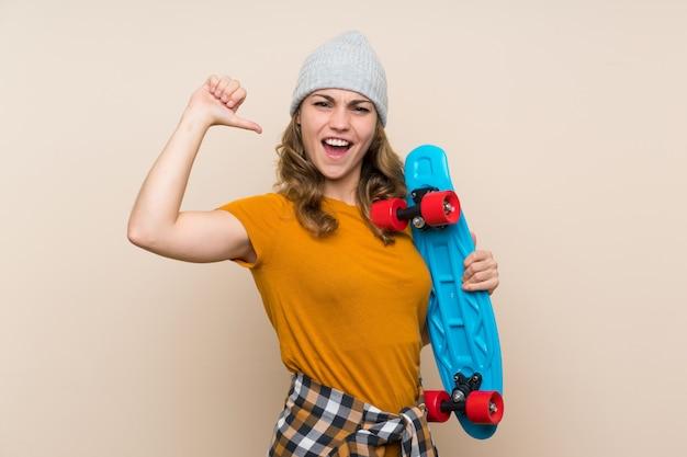 Menina loira jovem patinadora orgulhosa de si mesma sobre parede isolada