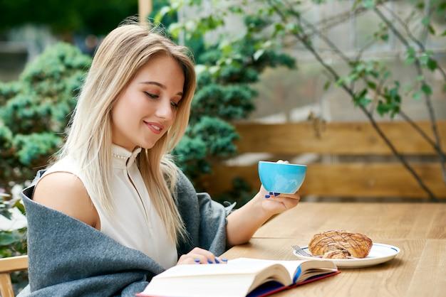 Menina loira, lendo um livro enquanto bebia café no salão do café ao ar livre.
