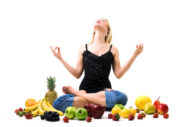 Menina loira meditando rodeado de frutas