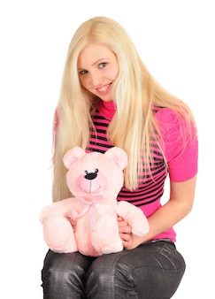 Menina loira misteriosa com um urso de brinquedo e um doce em um vestido rosa posando em um branco