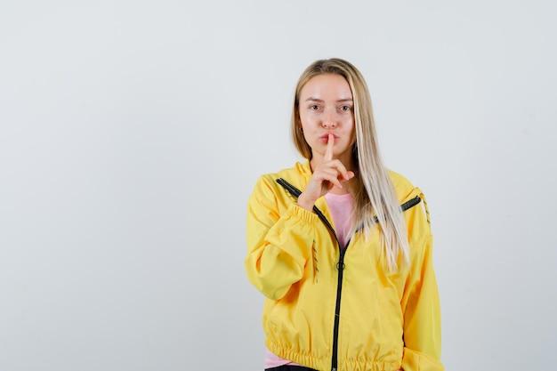 Menina loira mostrando gesto de silêncio em jaqueta amarela e parecendo sensata