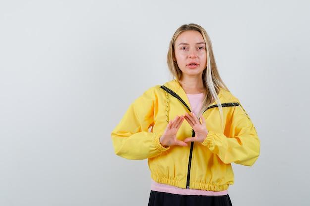 Menina loira mostrando gesto seguro em t-shirt rosa e jaqueta amarela e olhando sério.