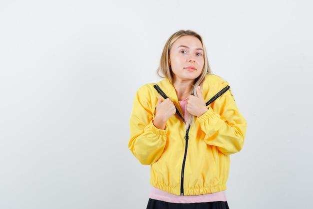 Menina loira mostrando os polegares para baixo com as duas mãos em uma camiseta rosa e jaqueta amarela e parecendo satisfeita