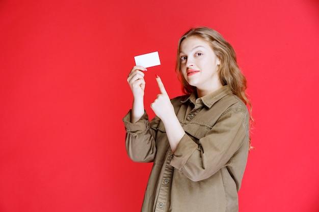 Menina loira mostrando seu cartão de visita e redes.