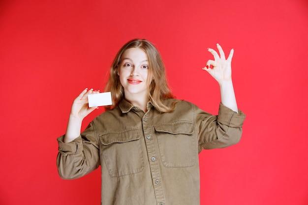 Menina loira mostrando seu cartão de visita e sinal de mão positiva.