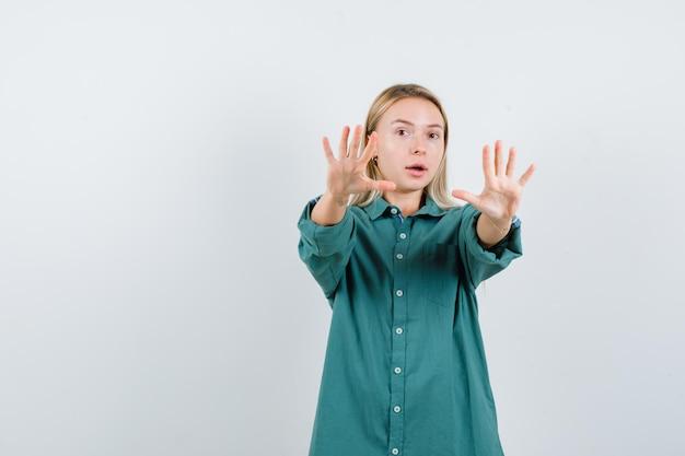 Menina loira mostrando sinais de stop na blusa verde e parecendo surpresa.