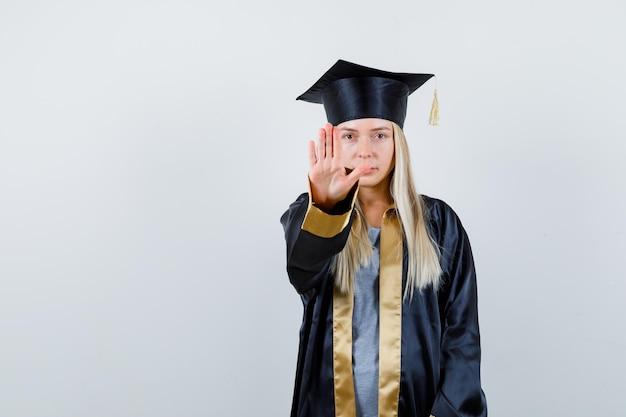Menina loira mostrando sinal de stop no vestido de formatura e boné e olhando sério.
