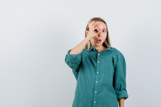 Menina loira mostrando sinal de tudo bem no olho na blusa verde e parecendo surpresa.